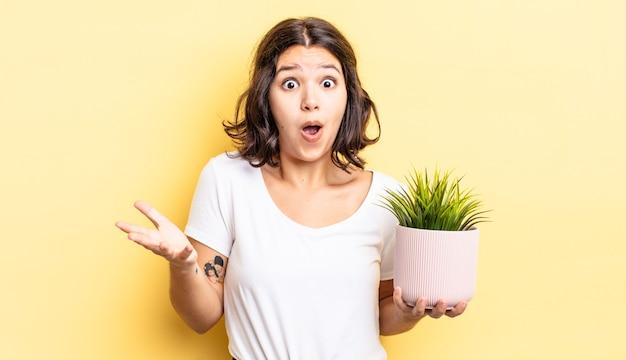 Jonge spaanse vrouw voelt zich extreem geschokt en verrast. groei concept
