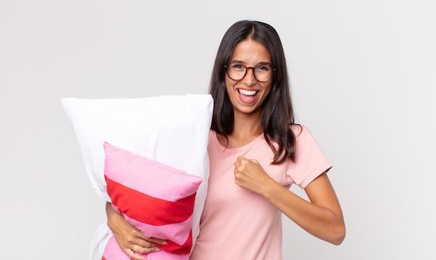 Jonge spaanse vrouw voelt zich gelukkig en staat voor een uitdaging of viert het dragen van een pyjama en een kussen