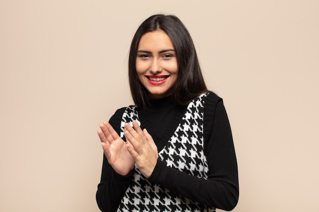 Jonge spaanse vrouw voelt zich gelukkig en succesvol, lacht en klapt in de handen en zegt gefeliciteerd met een applaus
