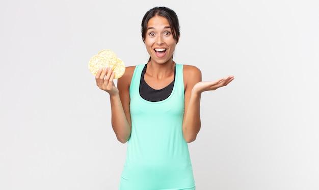 Jonge spaanse vrouw voelt zich gelukkig en verbaasd over iets ongelooflijks. fitness dieet concept