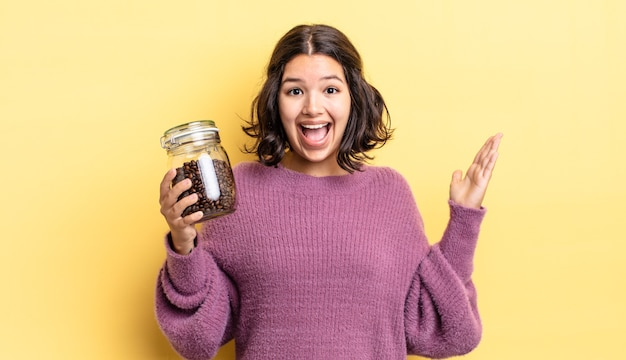 Jonge spaanse vrouw voelt zich gelukkig en verbaasd over iets ongelooflijks. koffiebonen concept
