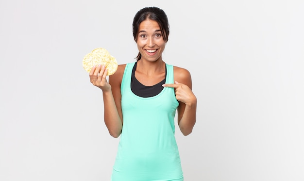 Jonge spaanse vrouw voelt zich gelukkig en wijst naar zichzelf met een opgewonden fitness dieet concept