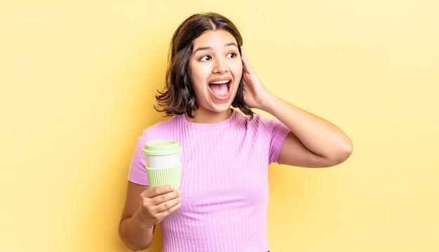 Jonge spaanse vrouw voelt zich gelukkig, opgewonden en verrast. afhaal koffie concept