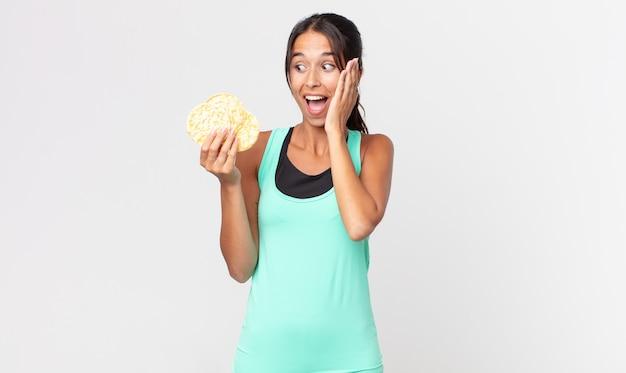 Jonge spaanse vrouw voelt zich gelukkig, opgewonden en verrast. fitness dieet concept