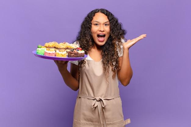 Jonge spaanse vrouw voelt zich gelukkig, opgewonden, verrast of geschokt, glimlacht en verbaasd over iets ongelooflijks. koken taarten concept