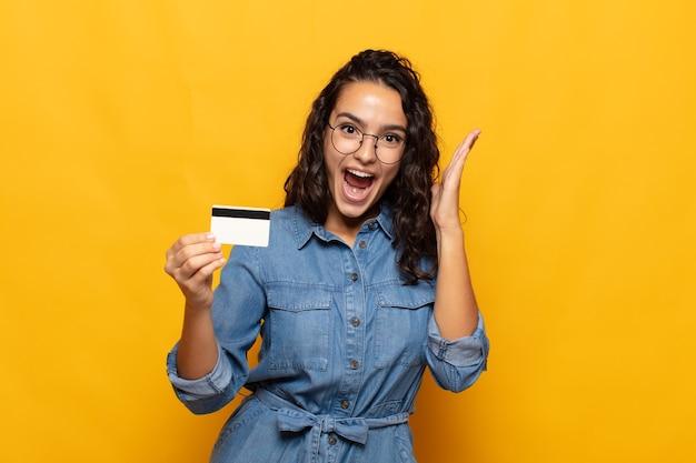 Jonge spaanse vrouw voelt zich gelukkig, opgewonden, verrast of geschokt, glimlacht en verbaasd over iets ongelooflijks unbeliev