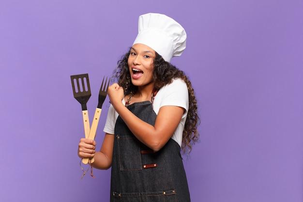 Jonge spaanse vrouw voelt zich gelukkig, positief en succesvol, gemotiveerd wanneer ze voor een uitdaging staat of goede resultaten viert. barbecue chef-kok concept