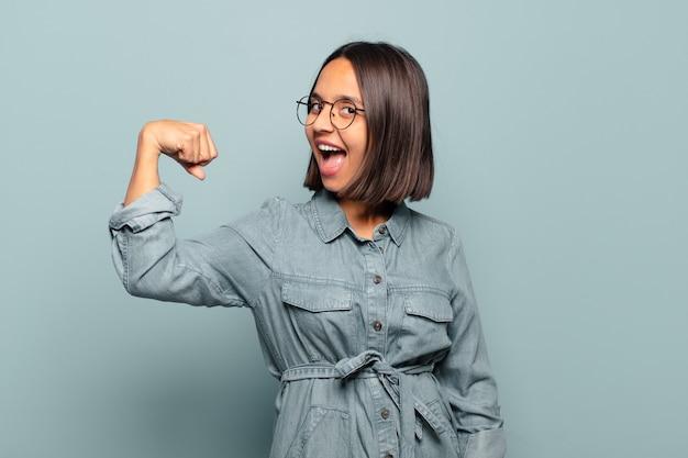 Jonge spaanse vrouw voelt zich gelukkig, tevreden en krachtig, buigt fit en gespierde biceps, ziet er sterk uit na de sportschool