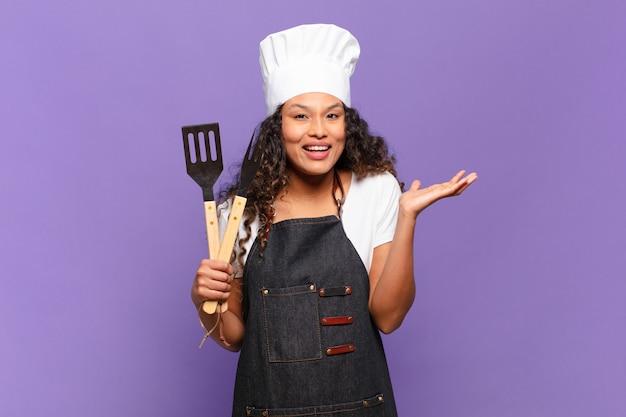 Jonge spaanse vrouw voelt zich gelukkig, verrast en opgewekt, glimlacht met een positieve houding en realiseert een oplossing of idee. barbecue chef-kok concept