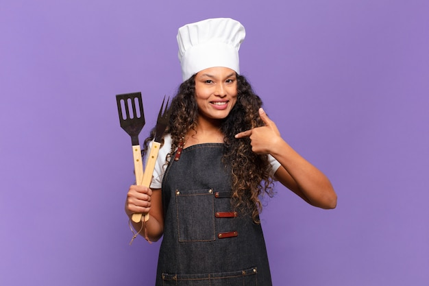 Jonge spaanse vrouw voelt zich gelukkig, verrast en trots, wijzend naar zichzelf met een opgewonden, verbaasde blik. barbecue chef-kok concept