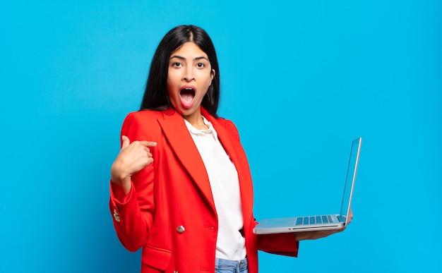 Jonge spaanse vrouw voelt zich gelukkig, verrast en trots, wijzend naar zichzelf met een opgewonden, verbaasde blik. laptopconcept