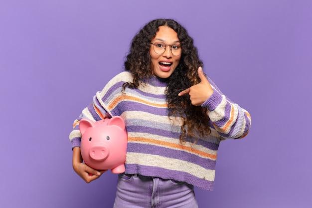 Jonge spaanse vrouw voelt zich gelukkig, verrast en trots, wijzend naar zichzelf met een opgewonden, verbaasde blik. spaarvarken concept
