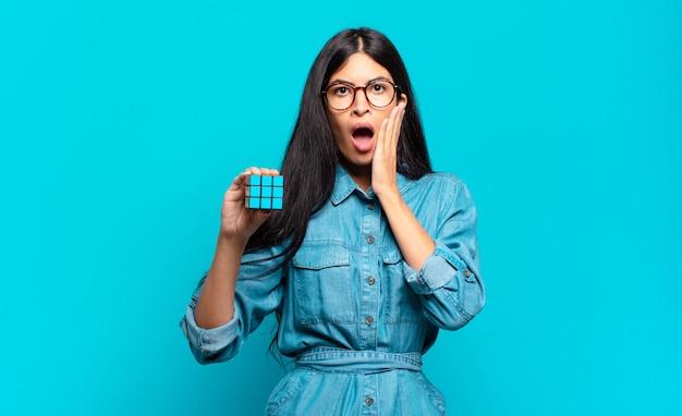 Jonge spaanse vrouw voelt zich geschokt en bang, ziet er doodsbang uit met open mond en handen op de wangen. intelligentie probleem concept