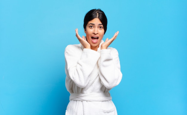 Jonge spaanse vrouw voelt zich geschokt en opgewonden, lachend, verbaasd en blij vanwege een onverwachte verrassing. badjas concept