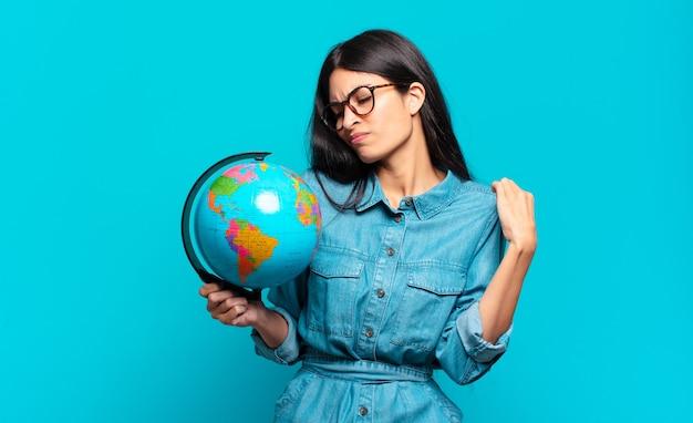 Jonge spaanse vrouw voelt zich gestrest, angstig, moe en gefrustreerd, trekt aan de nek van het shirt en ziet er gefrustreerd uit met een probleem. aarde planeet concept