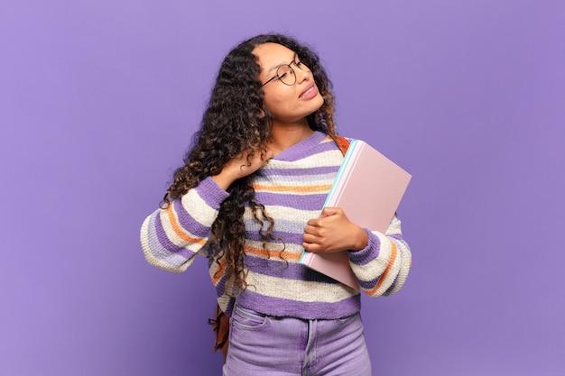 Jonge spaanse vrouw voelt zich gestrest, angstig, moe en gefrustreerd, trekt aan de nek van het shirt en ziet er gefrustreerd uit met een probleem. studentenconcept