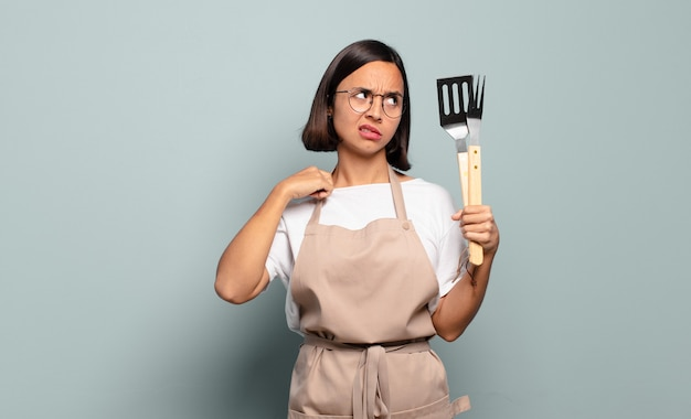 Jonge spaanse vrouw voelt zich gestrest, angstig, moe en gefrustreerd, trekt aan de nek van het shirt, ziet er gefrustreerd uit met een probleem