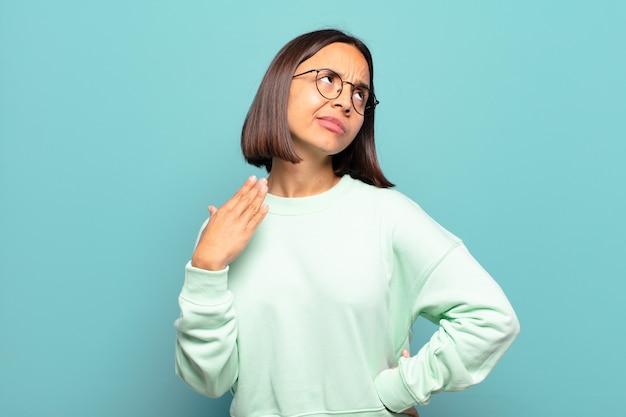 Jonge spaanse vrouw voelt zich gestrest, angstig, moe en gefrustreerd, trekt aan de nek van het shirt, ziet er gefrustreerd uit met problemen
