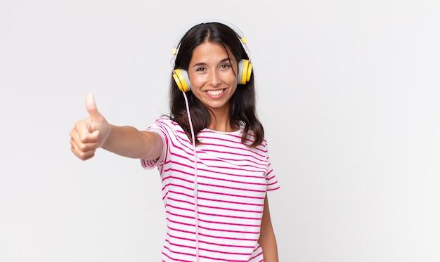 Jonge spaanse vrouw voelt zich trots, lacht positief met duimen omhoog en luistert naar muziek met een koptelefoon