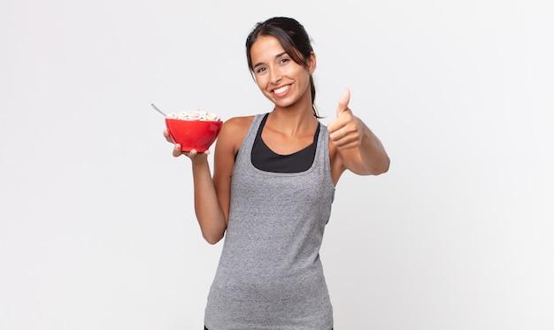 Jonge spaanse vrouw voelt zich trots, positief glimlachend met duimen omhoog. fitness dieet en ontbijt concept