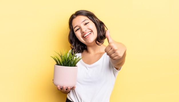Jonge spaanse vrouw voelt zich trots, positief glimlachend met duimen omhoog. groei concept