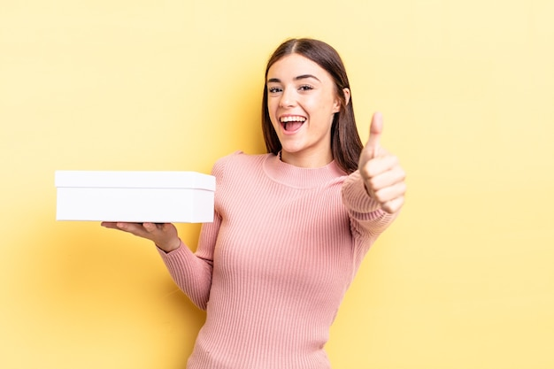 Jonge spaanse vrouw voelt zich trots, positief glimlachend met duimen omhoog. lege doos concept