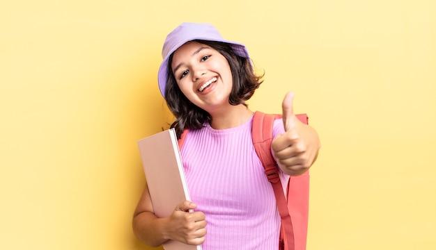 Jonge spaanse vrouw voelt zich trots, positief glimlachend met duimen omhoog. terug naar schoolconcept