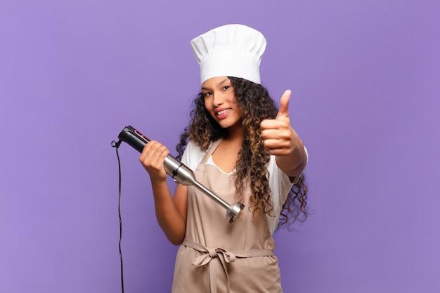 Jonge spaanse vrouw voelt zich trots, zorgeloos, zelfverzekerd en gelukkig, positief glimlachend met duimen omhoog. chef-kok concept