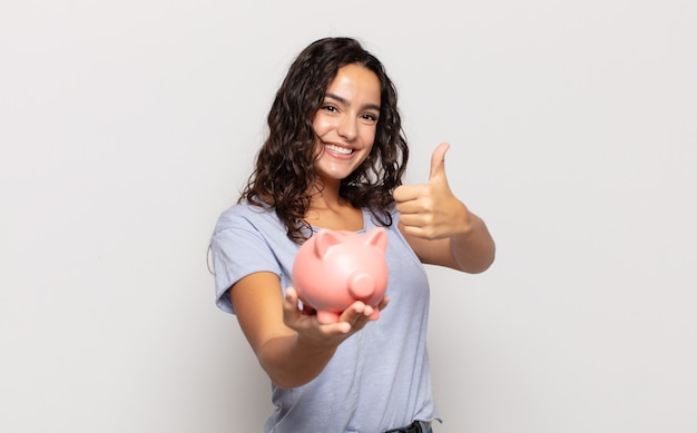 Jonge spaanse vrouw voelt zich trots, zorgeloos, zelfverzekerd en gelukkig, positief glimlachend met duimen omhoog