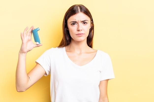 Jonge spaanse vrouw voelt zich verdrietig en zeurt met een ongelukkige blik en huilt. astma concept