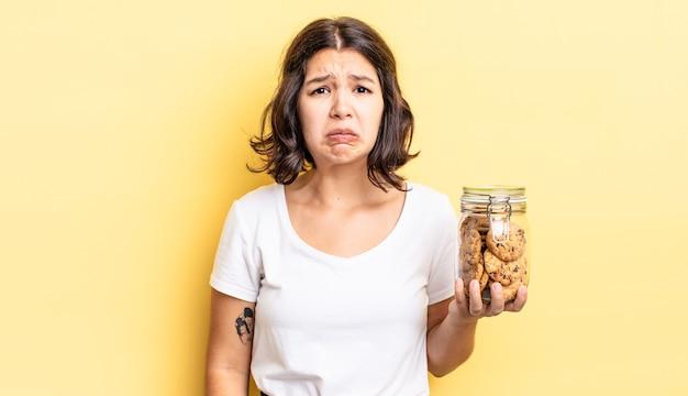 Jonge spaanse vrouw voelt zich verdrietig en zeurt met een ongelukkige blik en huilt. koekjes fles concept