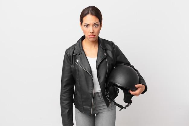 Jonge spaanse vrouw voelt zich verdrietig en zeurt met een ongelukkige blik en huilt. motorrijder concept