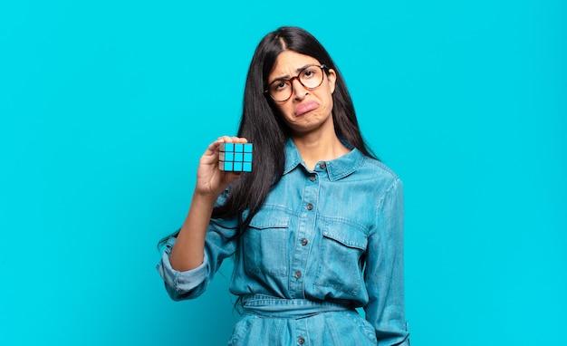 Jonge spaanse vrouw voelt zich verdrietig en zeurt met een ongelukkige blik, huilend met een negatieve en gefrustreerde houding. intelligentie probleem concept