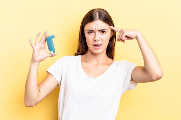 Jonge spaanse vrouw voelt zich verward en verbaasd en laat zien dat je gek bent. astma concept