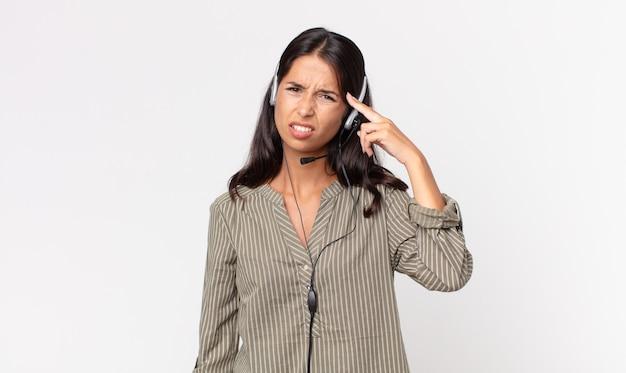 Jonge spaanse vrouw voelt zich verward en verbaasd en laat zien dat je gek bent met een headset. telemarketing concept