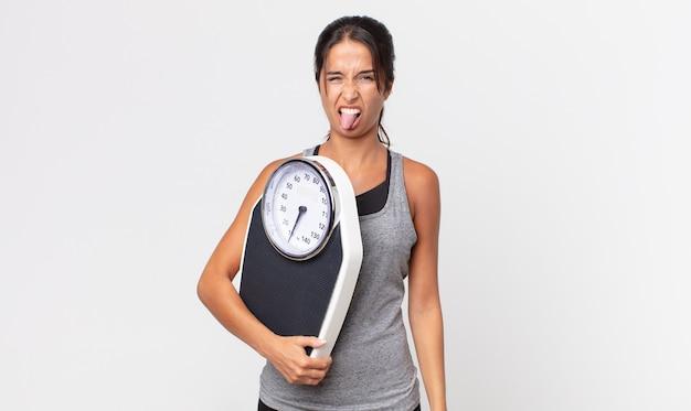 Jonge spaanse vrouw voelt zich walgelijk en geïrriteerd en tong uit en houdt een weegschaal vast. dieet concept