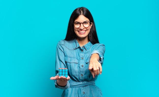Jonge spaanse vrouw wijzend met een tevreden, zelfverzekerde, vriendelijke glimlach, jou kiezen. intelligentie probleem concept
