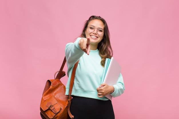 Jonge spaanse vrouw wijzend op camera met een tevreden, zelfverzekerde, vriendelijke glimlach, die jou kiest