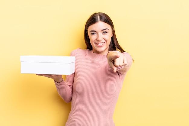 Jonge spaanse vrouw wijzend op de camera die jou kiest. lege doos concept