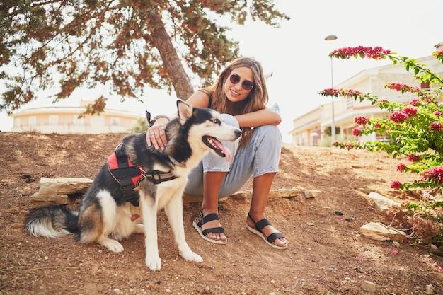 Jonge spaanse vrouw zit in het park met haar siberische husky