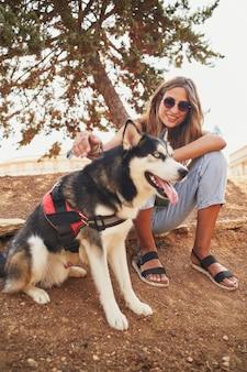 Jonge spaanse vrouw zit met haar siberische husky in park