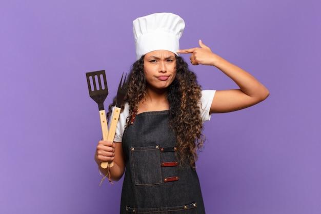 Jonge spaanse vrouwelijke chef-kok voelt zich verward en verbaasd