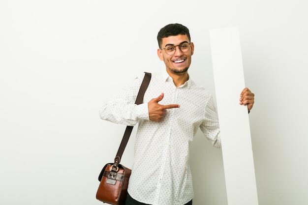 Jonge spaanse zakenman die een aanplakbiljet houdt