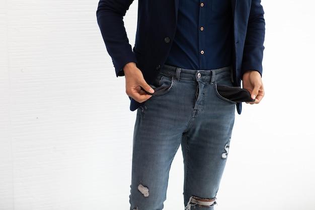 Jonge spaanse zakenman freelancer toont zijn lege zakken op een witte achtergrond.