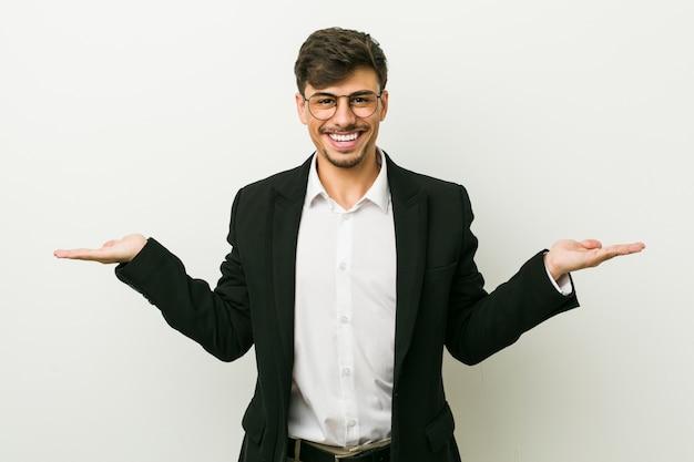 Jonge spaanse zakenman maakt schaal met armen, voelt zich gelukkig en zelfverzekerd.
