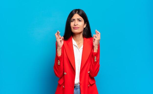 Jonge spaanse zakenvrouw angstig vingers kruisen en hopen op geluk met een bezorgde blik