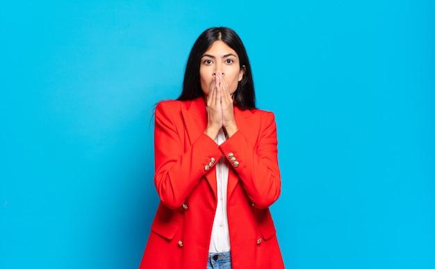 Jonge spaanse zakenvrouw blij en opgewonden, verrast en verbaasd mond bedekt met handen, giechelend met een schattige uitdrukking