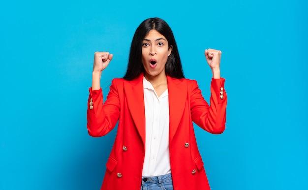 Jonge spaanse zakenvrouw die een ongelooflijk succes viert als een winnaar, er opgewonden en blij uitziet en zegt: neem dat!