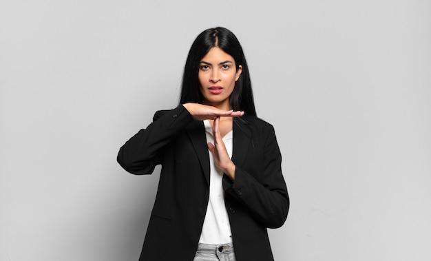 Jonge spaanse zakenvrouw die er serieus, streng, boos en ontevreden uitziet, waardoor een time-out teken wordt