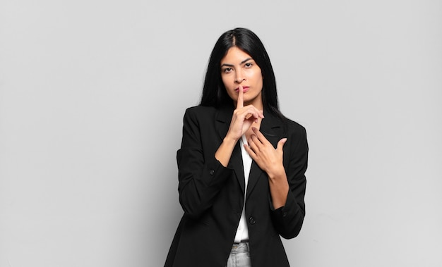 Jonge spaanse zakenvrouw die er serieus uitziet en kruist met de vinger tegen de lippen gedrukt die stilte of stilte eist en een geheim bewaart